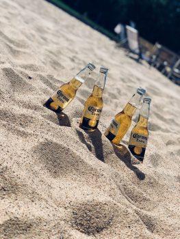 Bottles of beer on sand.